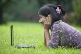 Asian student using laptop outdoor — Stock Photo