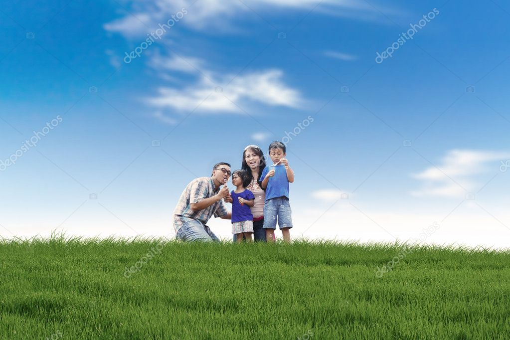Asian family playing with bubble in meadow — Stock Photo #11165387