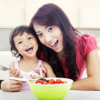 Smiling mom and daughter in kitchen — Stock Photo #11413376