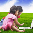 Asian sibling using laptop outdoor — Stock Photo