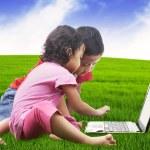 Asian sibling using laptop outdoor — Stock Photo