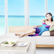 Asian woman watching tv by the beach — Stock Photo #11871954