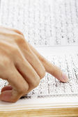 Hand pointing at paragraph of quran — Stock Photo
