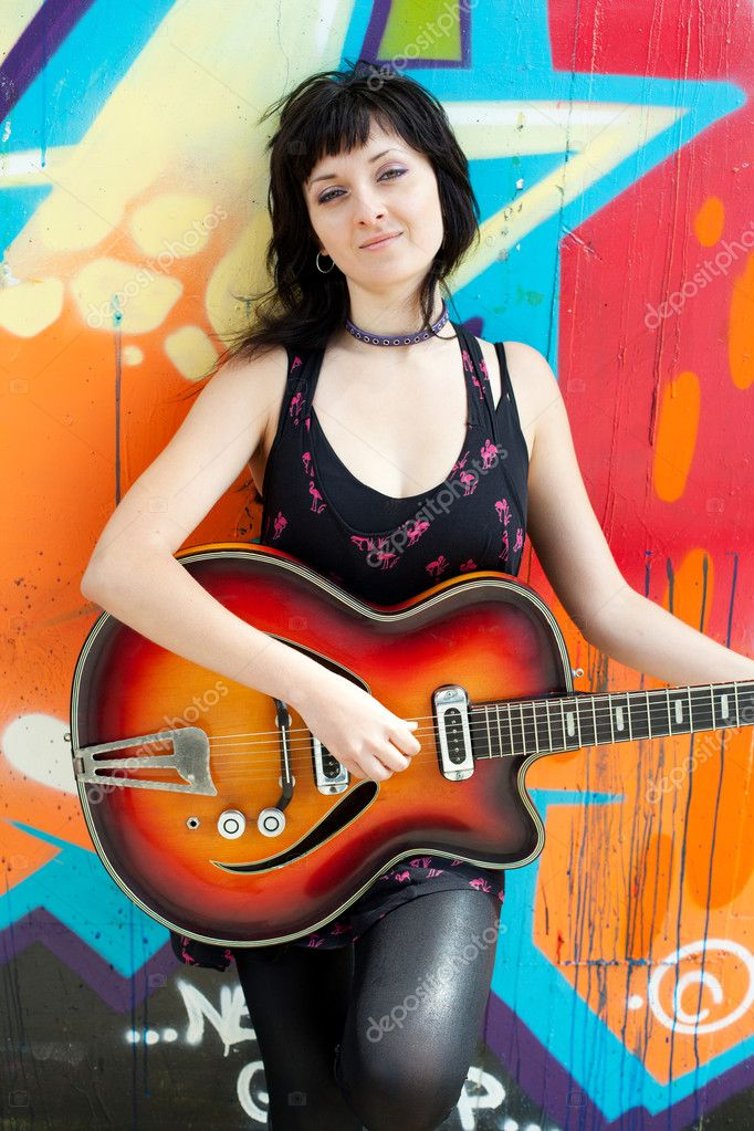 Closeup portrait of a happy young girl with retro guitar and graffiti on background — Stock Photo #10991845