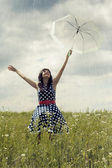 Happy young girl with umbrella in the field — Stock Photo