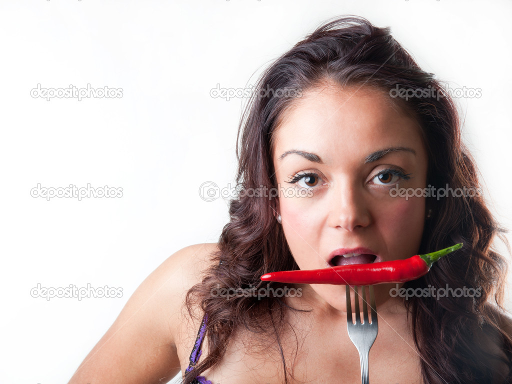 Young brunette woman biting a red chilli  Stock Photo #10757793