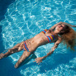 The beautiful girl floats in pool — Stock Photo
