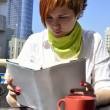 Young woman in a cafe reading a book — Stock Photo #11326385