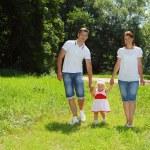 Happy family walking in park — Stock Photo
