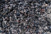 Volcanic black stones on the beach — Stock Photo