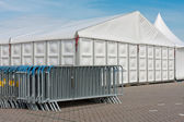 Crush barriers near a big marquee — Stock Photo