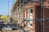 Byggarbetsplats med familj hus i byggnadsställningar — Stockfoto