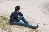 Mujer relajante en la playa cerca de la orilla del mar — Foto de Stock