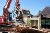 Demolition of a building with a excavator — Stockfoto