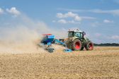 Tractor with a sowing machine working in the field — Stock Photo