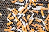 Cigarettes in a big iron ashtray — Stock Photo