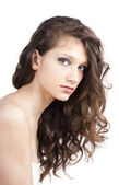 Pretty young woman in white dress with curly hair — Stock Photo