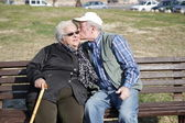 Elderly men kisses the old women - love concep — Stock Photo