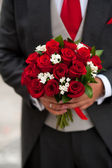 Groom showing her rose bouquet — Stock Photo