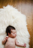 Sweet newborn lying on a white blanket — Stock Photo
