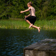 Boy running off dock into lake — Stock Photo