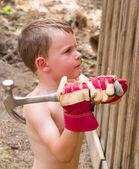 Chlapec pomáhá kladivem hřebíky — Stock fotografie