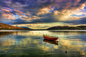 Traditional fishing red boat at sunset time in lake — Stock Photo