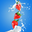 Juicy strawberries in milk splashes - Stock Photo