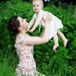 Little pretty baby on a green lawn with mom — ストック写真