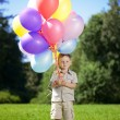 Ñhild with a bunch of balloons in their hands — Stock Photo
