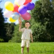Child with a bunch of balloons in their hands — Stock Photo