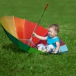 Stock Photo: Little boy with a big rainbow umbrella