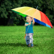 Little boy with a big rainbow umbrella — Stockfoto