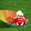 Little girl with a rainbow umbrella in park — Stock Photo #11292064