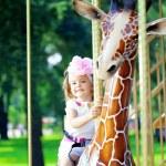 Girl riding on a carousel — Stock Photo #11292119