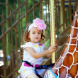 Girl riding on a carousel - Stock Photo