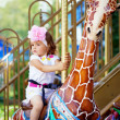 Girl riding on a carousel — Stock Photo