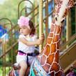 Girl riding on a carousel — Stock Photo