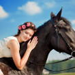 Woman on a horse by the sea - Stock Photo