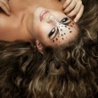 Girl with an unusual make-up as a leopard and luxury hair — Stock Photo #11292309