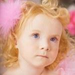 Girl in the nursery in pink dress — Stock Photo