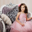 Child on a chair in a nice dress — Stock Photo