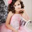 Stock Photo: Child on a chair in a nice dress