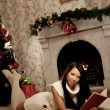 Girl lying near the fireplace and reads a book — ストック写真