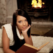 Girl lying near the fireplace and reads a book — Foto de Stock
