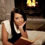 chica miente cerca de la chimenea y Lee un libro — Foto de Stock