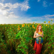Red-haired woman with sunflowers - Stock Photo
