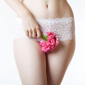 Abdomen and thighs with a bunch of flowers — Stock Photo