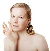 Girl puts on skin cream — Stock Photo