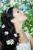 Beautiful bride in a blossoming garden — Stock Photo